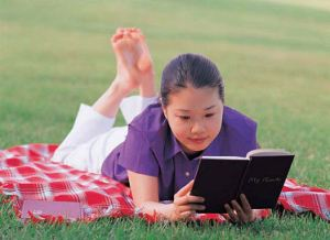 Young woman lying on a lawn reading a book uid 1531307